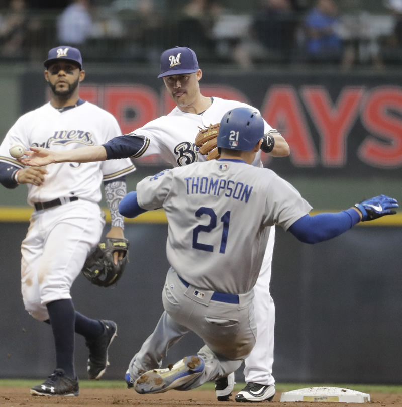 Milwaukee Brewers' Jake Elmore forces an out at second on Los Angeles Dodgers' Trayce Thompson as Elmore turns a double play on a ball hit by Yasmani Grandal during the fourth inning of a baseball game in Milwaukee. (AP Photo/Morry Gash)